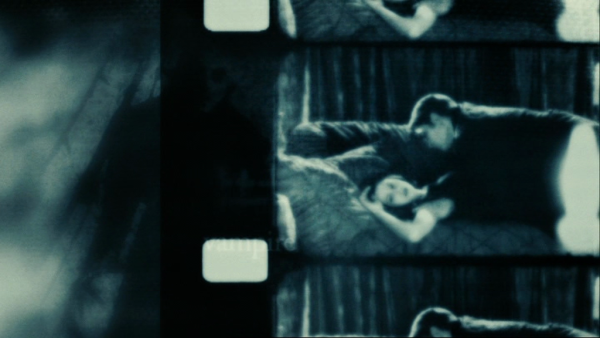 Black and white scene from Twilight that looks like an old-fashioned film strip with Edward lying on top of Bella on a bed with her face turned towards the viewer.